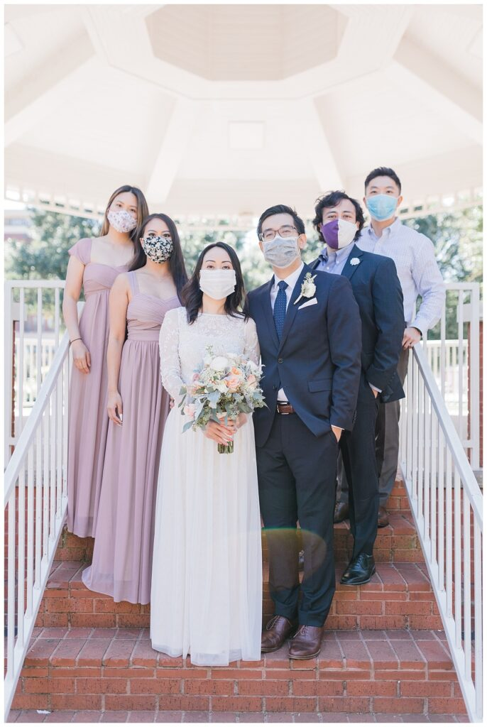 Bride in minimal, elegant white dress poses with bridal party under gazebo at Haggard Park in Plano, TX for bridal party portraits by wedding photographer Jenny Bui of Picture Bouquet Studio, a Dallas based wedding photography studio.