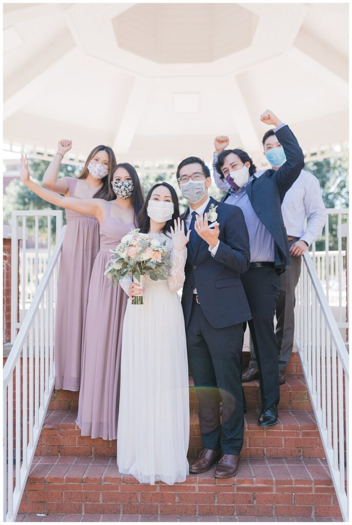 Bride in elegant, minimal white wedding dress and groom poses showing wedding rings with bridal party cheering in the background under gazebo at Haggard Park in Plano, TX for bridal party portraits by wedding photographer Jenny Bui of Picture Bouquet Studio, a Dallas based wedding photography studio.