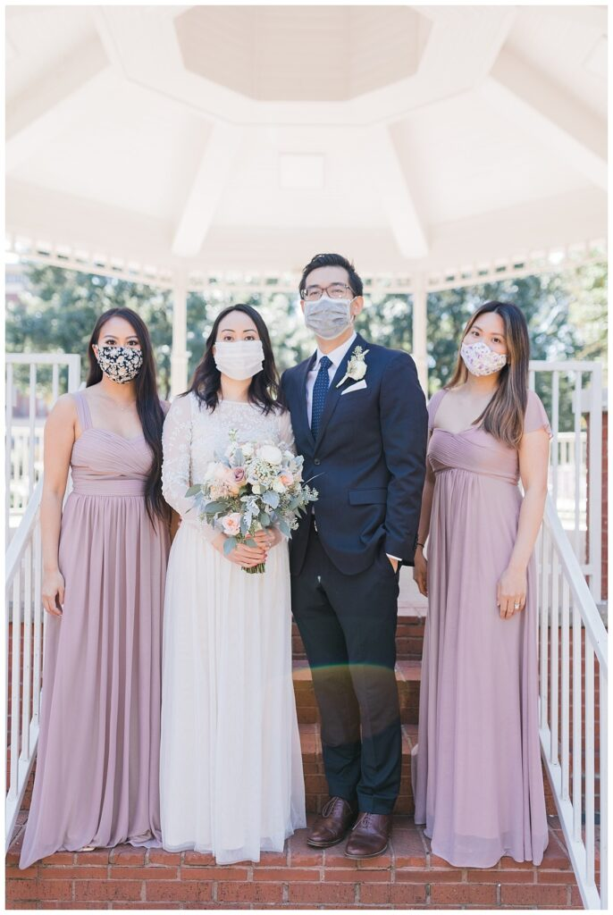 Bride in elegant, minimal white wedding dress poses with groom and bridesmaids in long lavender silk dresses under gazebo at Haggard Park in Plano, TX for bridal party portraits by wedding photographer Jenny Bui of Picture Bouquet Studio, a Dallas based wedding photography studio.