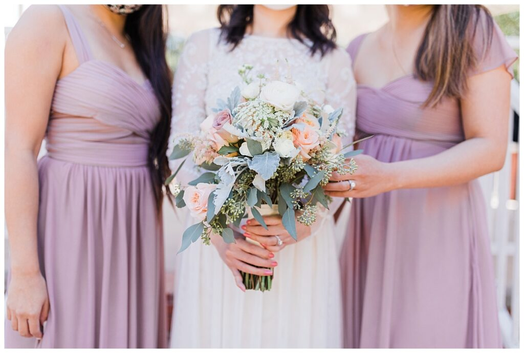 Romantic soft orange wedding day bouquet close up under gazebo at Haggard Park in Plano, TX for bridal party portraits by wedding photographer Jenny Bui of Picture Bouquet Studio, a Dallas based wedding photography studio.