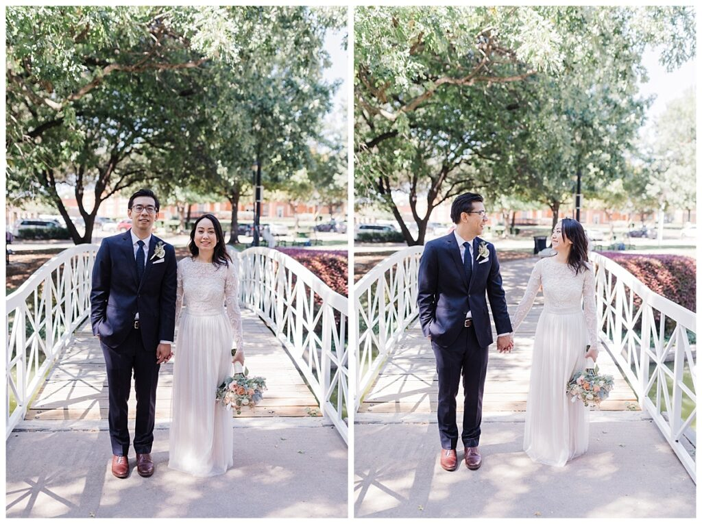 Bride in elegant, lace, minimal white dress poses with groom in navy suit on bridge at Haggard Park in Plano, TX for bridal party portraits by wedding photographer Jenny Bui of Picture Bouquet Studio, a Dallas based wedding photography studio.