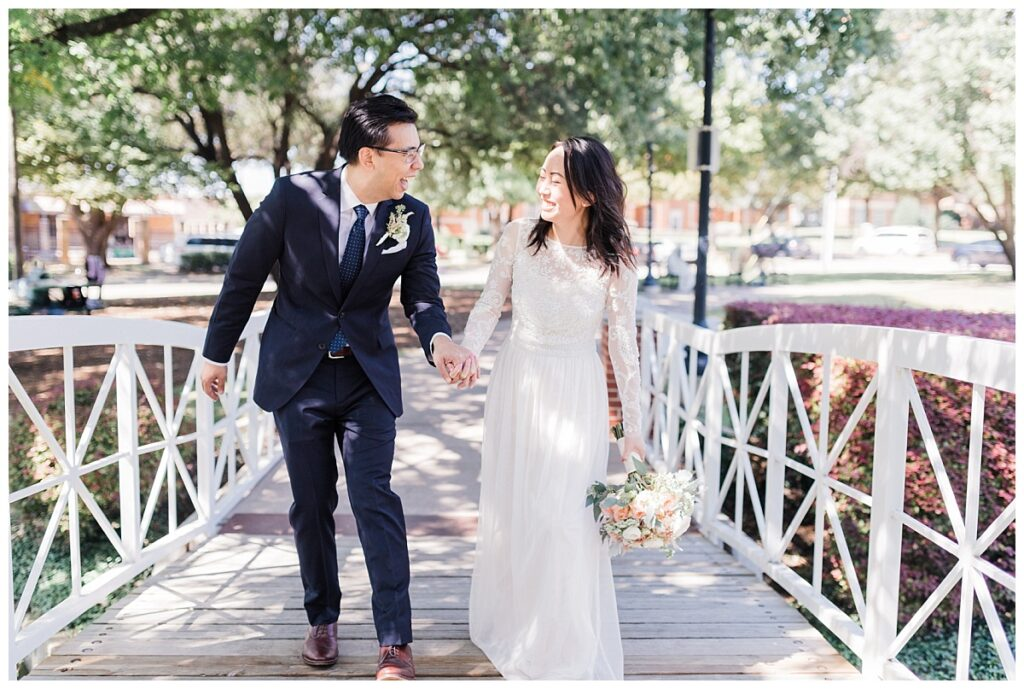 Bride in elegant, lace, minimal white dress smiles with groom in navy suit on bridge at Haggard Park in Plano, TX for bridal party portraits by wedding photographer Jenny Bui of Picture Bouquet Studio, a Dallas based wedding photography studio.