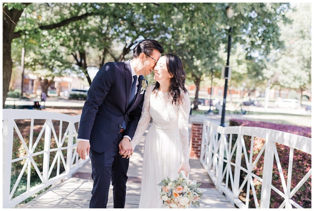 Bride in elegant, lace, minimal white dress shares laugh with groom in navy suit on bridge at Haggard Park in Plano, TX for bridal party portraits by wedding photographer Jenny Bui of Picture Bouquet Studio, a Dallas based wedding photography studio.