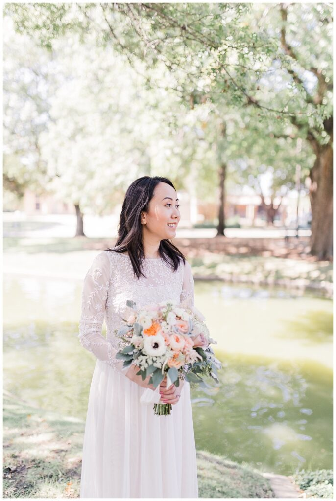 Bride in elegant, white lace minimal wedding dress poses with gorgeous soft orange bouquet in front of pond at Haggard Park in Plano, TX for bridal party portraits by wedding photographer Jenny Bui of Picture Bouquet Studio, a Dallas based wedding photography studio.