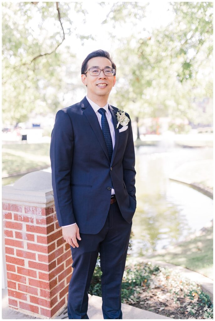 Groom in navy suit poses in front of pond at Haggard Park in Plano, TX for bridal party portraits by wedding photographer Jenny Bui of Picture Bouquet Studio, a Dallas based wedding photography studio.