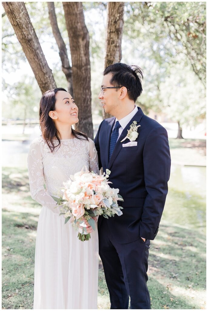 Bride in elegant, lace, minimal white dress gazes at groom in navy suit in front of pond at Haggard Park in Plano, TX for bridal party portraits by wedding photographer Jenny Bui of Picture Bouquet Studio, a Dallas based wedding photography studio.