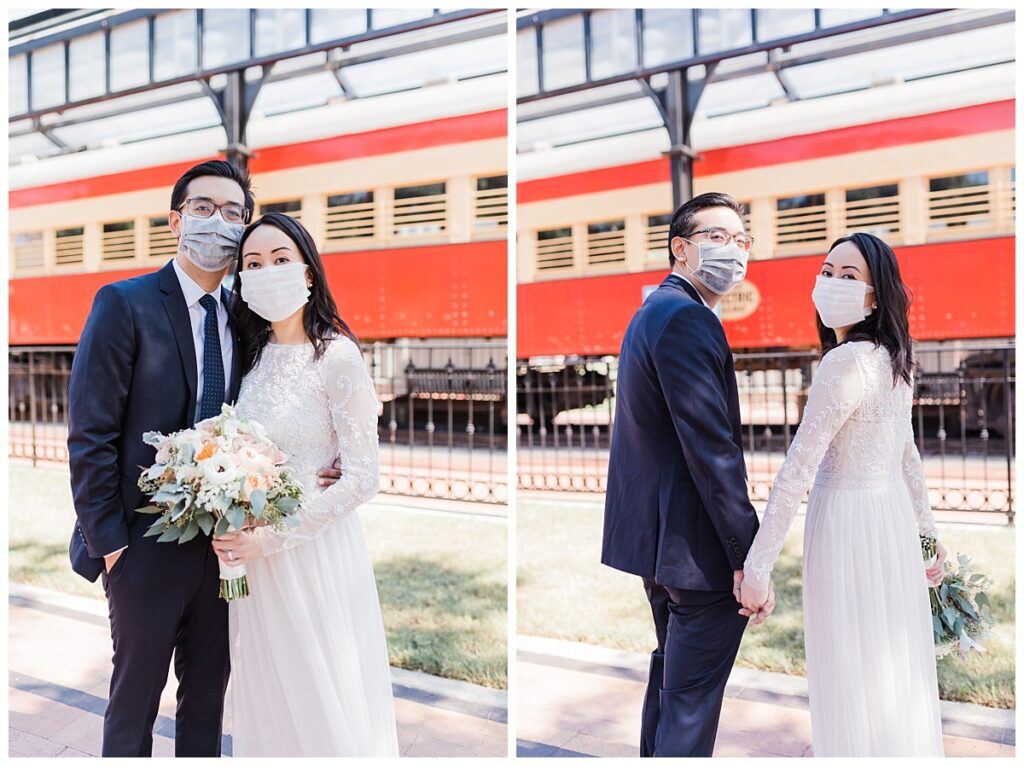 Bride in elegant, lace, white minimal dress poses with groom in navy suit holding soft orange bouquet in front of red train at Haggard Park in Plano, TX for bridal party portraits by wedding photographer Jenny Bui of Picture Bouquet Studio, a Dallas based wedding photography studio.