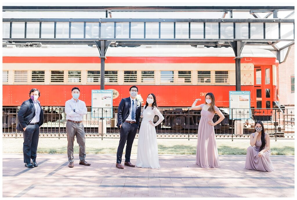 Bride in elegant, lace, white minimal dress holding soft orange bouquet and groom in navy suit poses with bridal party in front of red train at Haggard Park in Plano, TX for bridal party portraits by wedding photographer Jenny Bui of Picture Bouquet Studio, a Dallas based wedding photography studio.