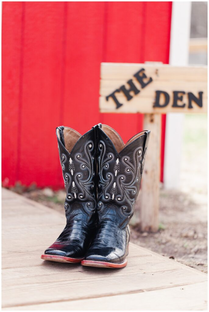 Wedding detail from outdoor Texas styled wedding of groom's wedding day boots posed in front of the groom's dressing room at Fort Worth Country Memorial Wedding Venue photographed by Dallas wedding photographer Jenny Bui of Picture Bouquet Studio.