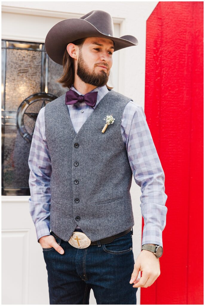 Groom poses in purple checkered shirt and purple bowtie with wedding day cowboy hat for outdoor Texas styled wedding at Fort Worth Country Memorial Wedding Venue photographed by Dallas wedding photographer Jenny Bui of Picture Bouquet Studio.