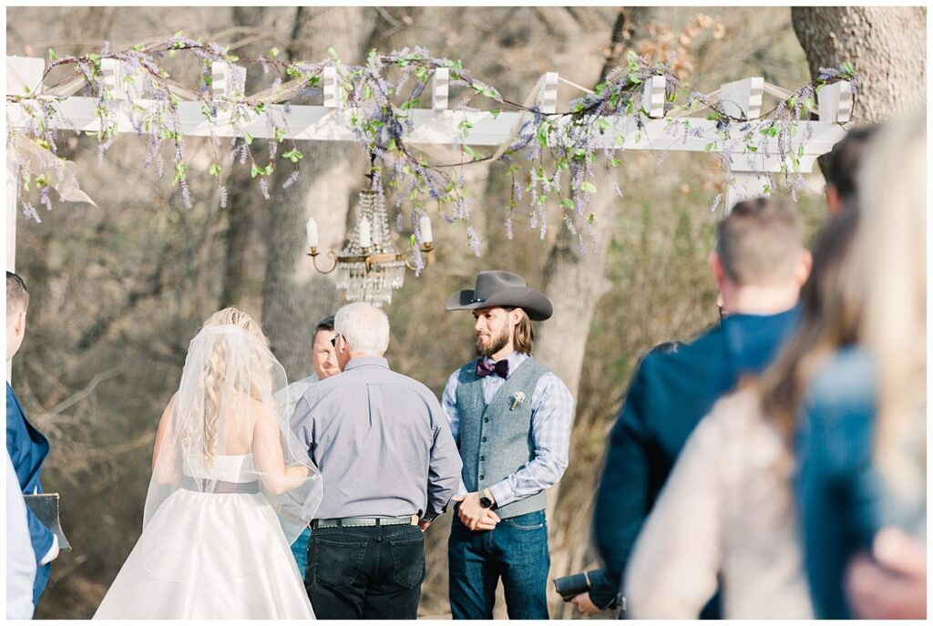 Texas styled groom gazing at bride as she walks down the aisle for outdoor Texas styled wedding at Fort Worth Country Memorial Wedding Venue photographed by Dallas wedding photographer Jenny Bui of Picture Bouquet Studio.
