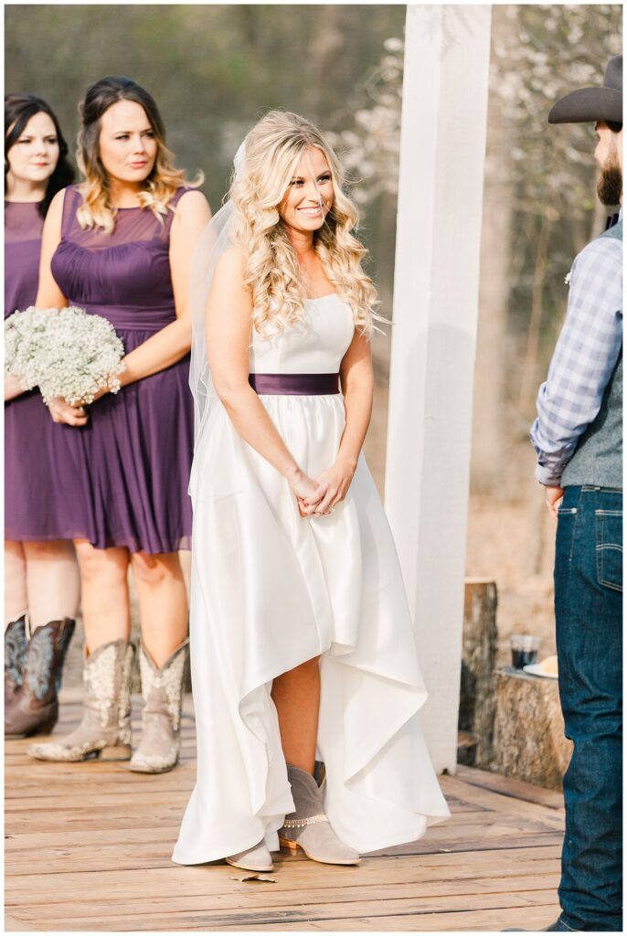 Texas styled bride smiling at groom at wedding ceremony for outdoor Texas styled wedding at Fort Worth Country Memorial Wedding Venue photographed by Dallas wedding photographer Jenny Bui of Picture Bouquet Studio.