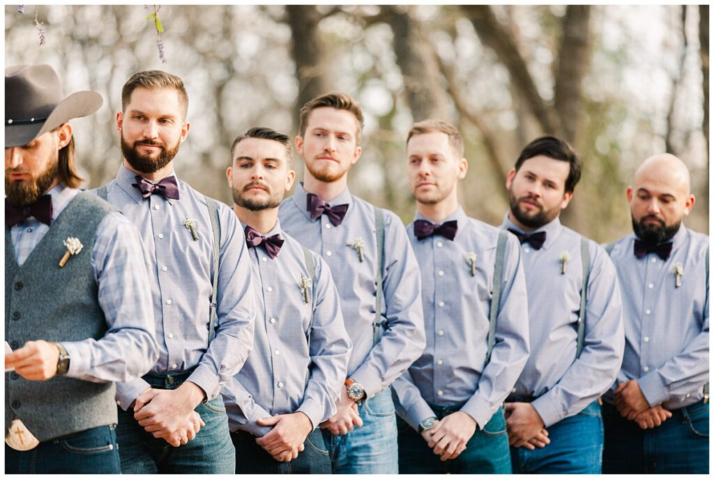 Texas styled groomsmen in bowties and bullet boutonnieres looks on as groom read vows for outdoor Texas styled wedding at Fort Worth Country Memorial Wedding Venue photographed by Dallas wedding photographer Jenny Bui of Picture Bouquet Studio.
