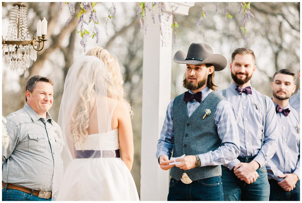 Groom reading vow to Texas styled bride for outdoor Texas styled wedding at Fort Worth Country Memorial Wedding Venue photographed by Dallas wedding photographer Jenny Bui of Picture Bouquet Studio.