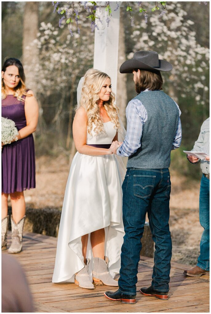 Country styled bride and groom holding hands for outdoor Texas styled wedding at Fort Worth Country Memorial Wedding Venue photographed by Dallas wedding photographer Jenny Bui of Picture Bouquet Studio.