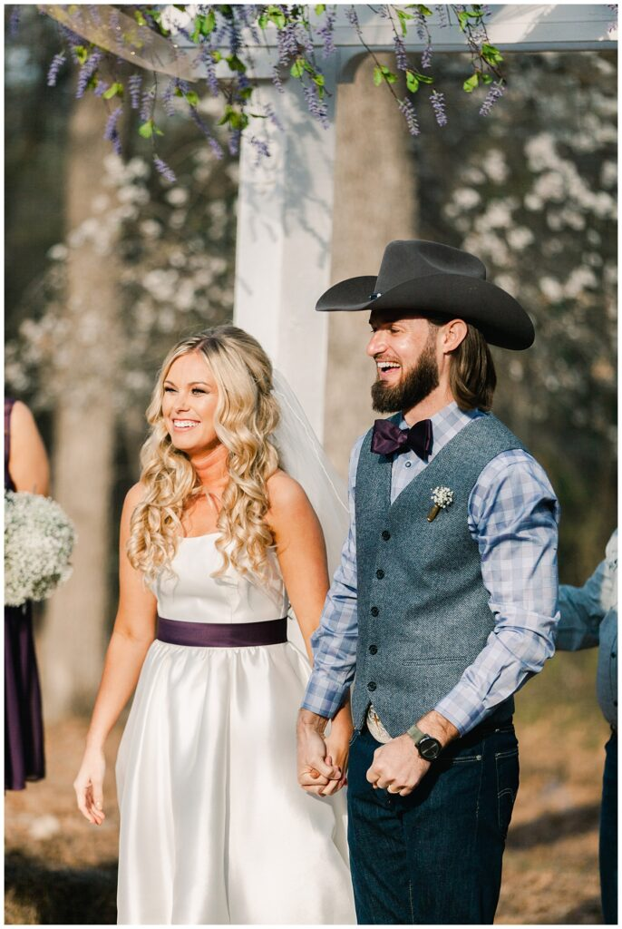 Texas styled bride and groom laughing as they walk down the aisle for outdoor Texas styled wedding at Fort Worth Country Memorial Wedding Venue photographed by Dallas wedding photographer Jenny Bui of Picture Bouquet Studio.