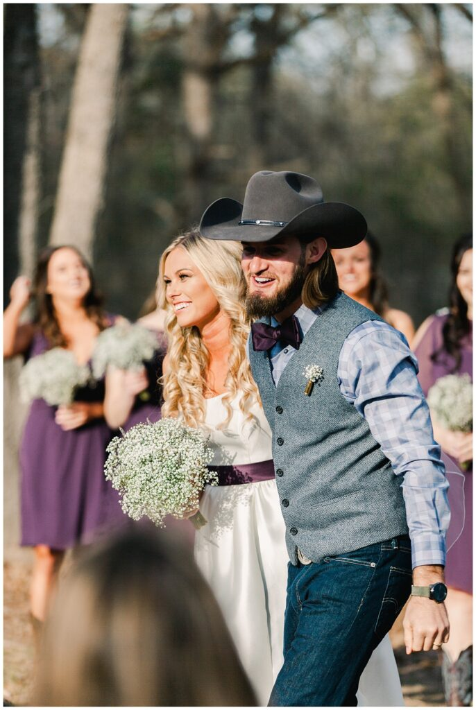 Texas styled bride and groom walking down aisle for outdoor Texas styled wedding at Fort Worth Country Memorial Wedding Venue photographed by Dallas wedding photographer Jenny Bui of Picture Bouquet Studio.