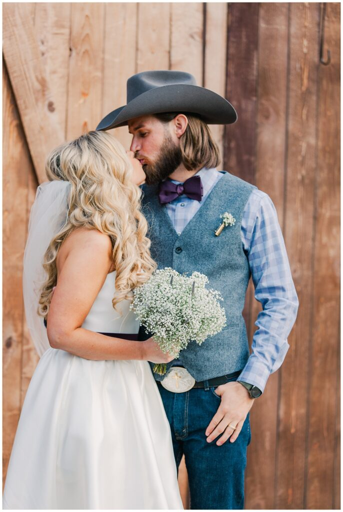 Texas bride and groom kisses in front of barn door for outdoor Texas styled wedding at Fort Worth Country Memorial Wedding Venue photographed by Dallas wedding photographer Jenny Bui of Picture Bouquet Studio.