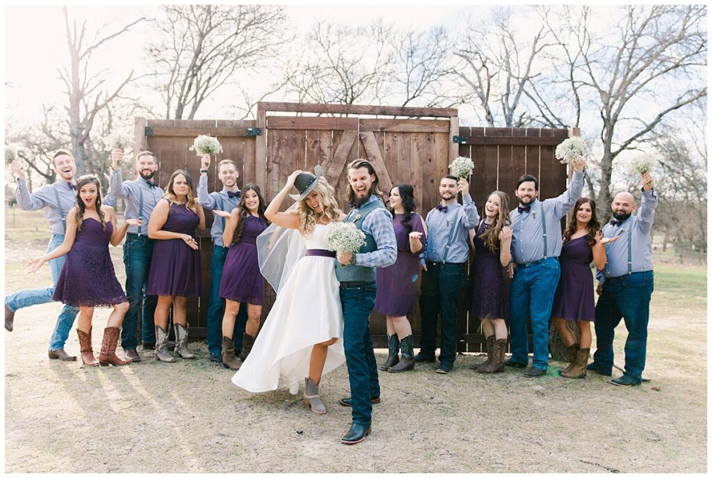 Texas styled bridal party in cowboy boots and bowties poses in front of barn door for bridal party portraits for outdoor Texas styled wedding at Fort Worth Country Memorial Wedding Venue photographed by Dallas wedding photographer Jenny Bui of Picture Bouquet Studio.
