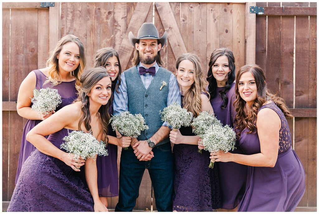 Texas styled bridesmaid in purple dresses and cowboy boots  poses in front of barn door with groom in cowboy hat for bridal party portraits for outdoor Texas styled wedding at Fort Worth Country Memorial Wedding Venue photographed by Dallas wedding photographer Jenny Bui of Picture Bouquet Studio.