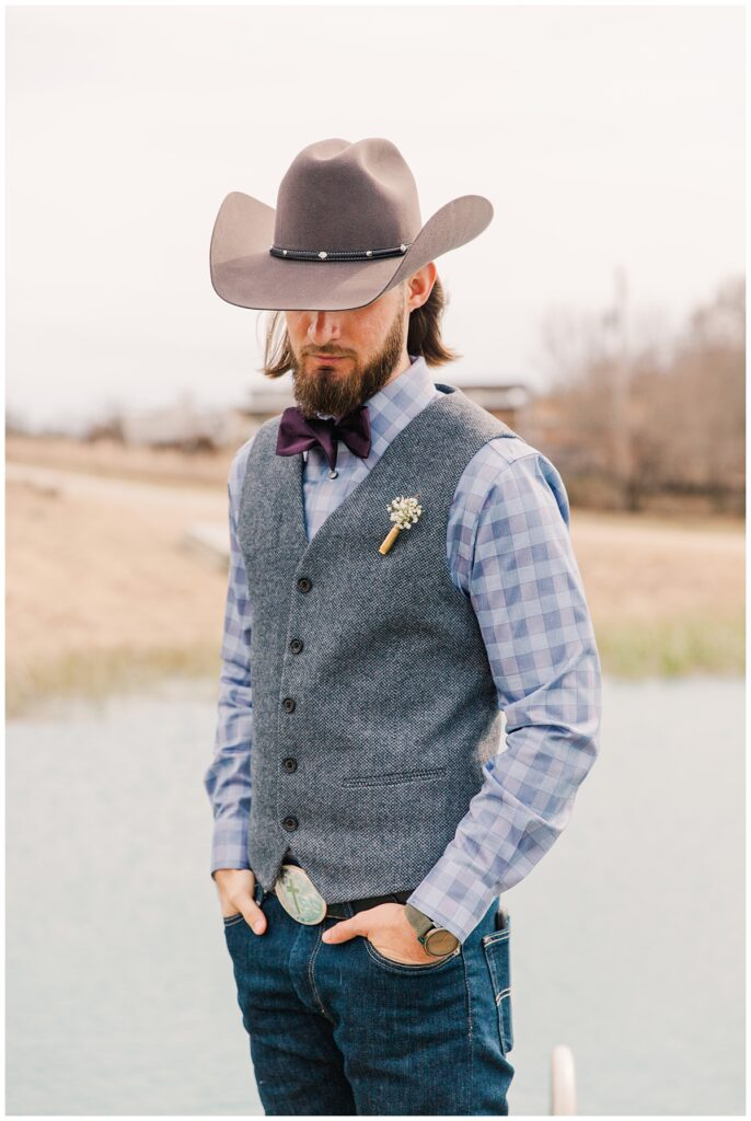 Groom poses in front of lake waiting for first look for outdoor Texas styled wedding at Fort Worth Country Memorial Wedding Venue photographed by Dallas wedding photographer Jenny Bui of Picture Bouquet Studio.