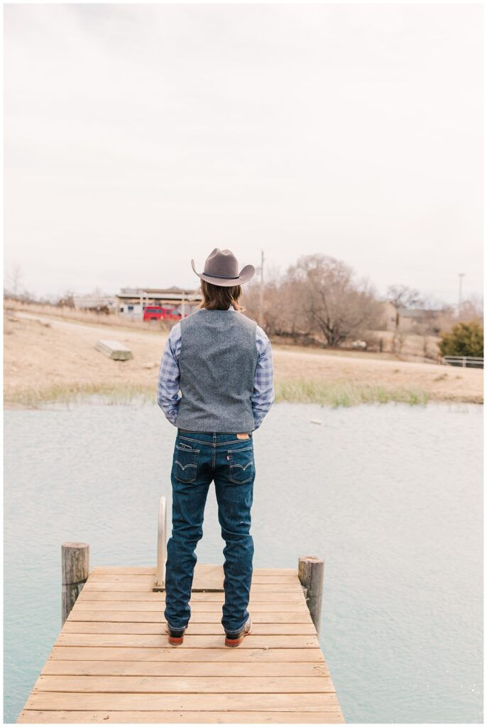 Groom waiting at end of pier for first look for outdoor Texas styled wedding at Fort Worth Country Memorial Wedding Venue photographed by Dallas wedding photographer Jenny Bui of Picture Bouquet Studio.