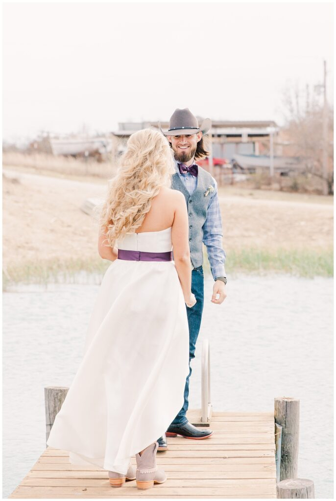 Groom in cowboy hat turns around for first look for outdoor Texas styled wedding at Fort Worth Country Memorial Wedding Venue photographed by Dallas wedding photographer Jenny Bui of Picture Bouquet Studio.