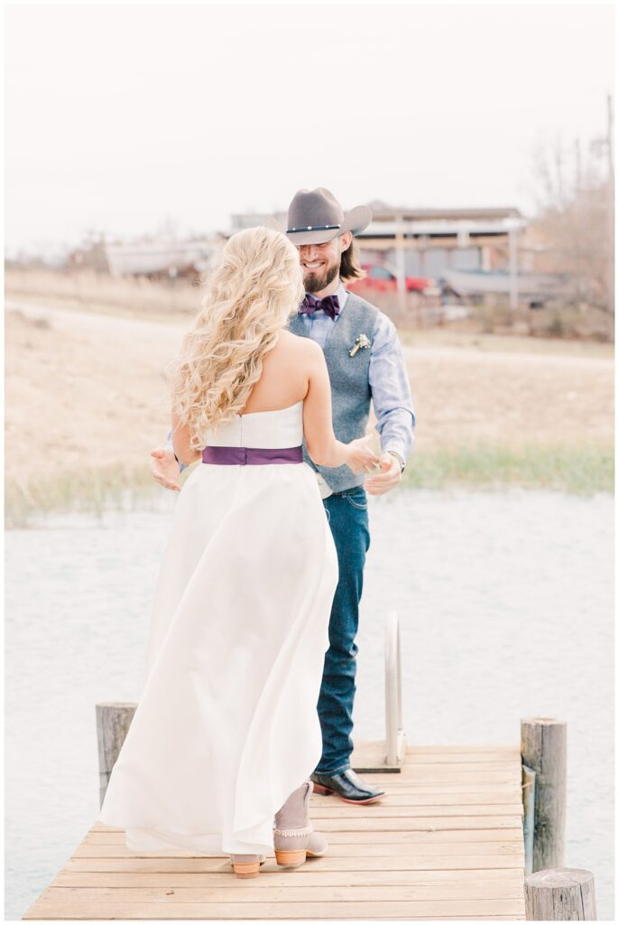 Groom in cowboy hat and bride in cowboy boots first look for outdoor Texas styled wedding at Fort Worth Country Memorial Wedding Venue photographed by Dallas wedding photographer Jenny Bui of Picture Bouquet Studio.