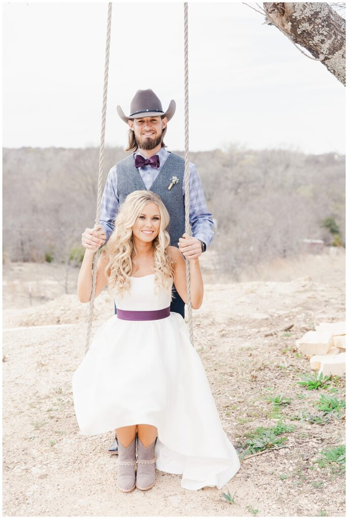 Texas styled bride sits on swing with groom in cowboy hat for outdoor Texas styled wedding at Fort Worth Country Memorial Wedding Venue photographed by Dallas wedding photographer Jenny Bui of Picture Bouquet Studio.