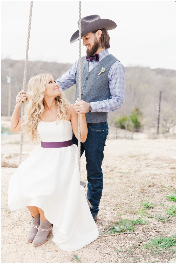 Texas styled bride and groom look at each other while bride is swinging on swing for outdoor Texas styled wedding at Fort Worth Country Memorial Wedding Venue photographed by Dallas wedding photographer Jenny Bui of Picture Bouquet Studio.