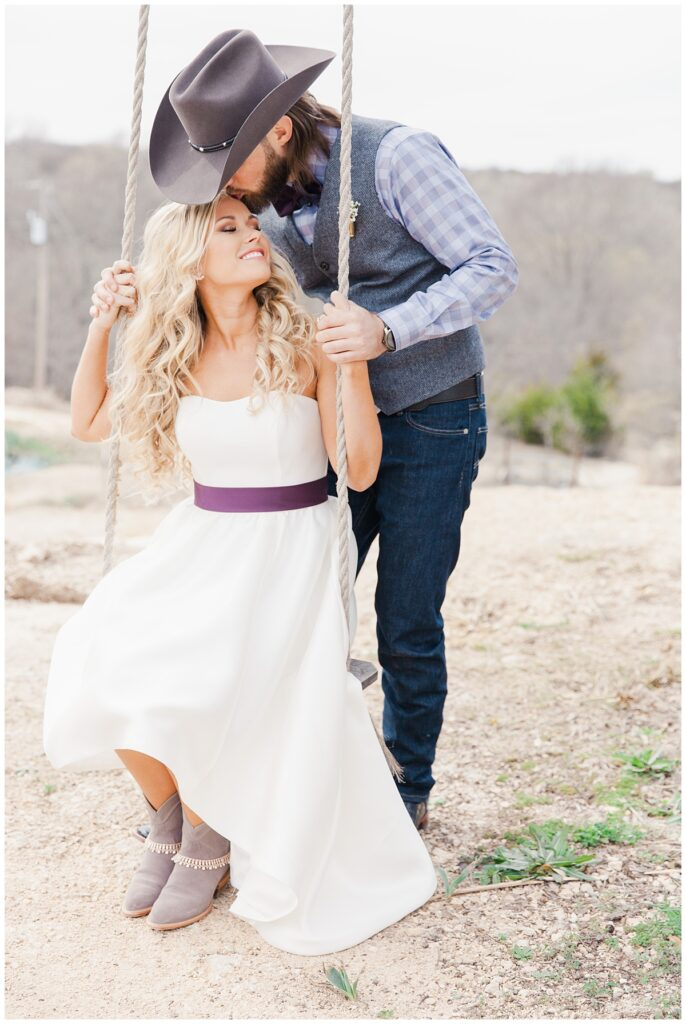 Texas styled groom in cowboy hat leans down and kisses bride on forehead for outdoor Texas styled wedding at Fort Worth Country Memorial Wedding Venue photographed by Dallas wedding photographer Jenny Bui of Picture Bouquet Studio.