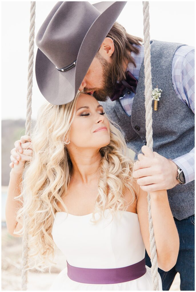 Cowboy groom leans down and kisses bride on forehead for outdoor Texas styled wedding at Fort Worth Country Memorial Wedding Venue photographed by Dallas wedding photographer Jenny Bui of Picture Bouquet Studio.