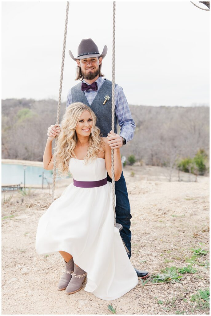 Texas styled bride and groom poses on swing for outdoor Texas styled wedding at Fort Worth Country Memorial Wedding Venue photographed by Dallas wedding photographer Jenny Bui of Picture Bouquet Studio.