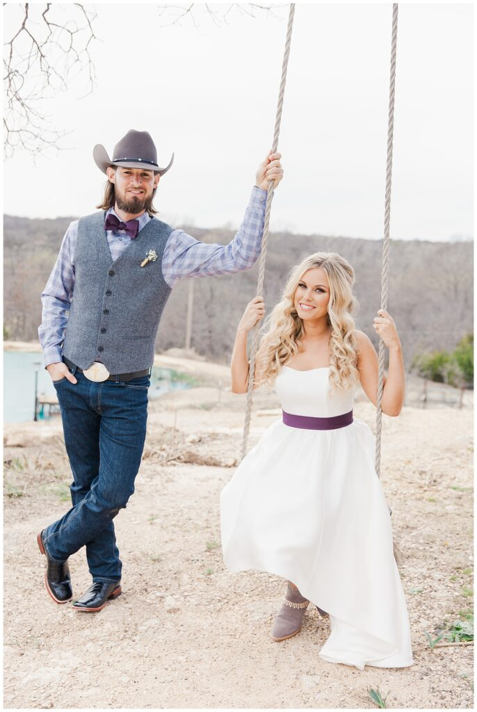 Texas styled bride and groom poses side by side on swing for outdoor Texas styled wedding at Fort Worth Country Memorial Wedding Venue photographed by Dallas wedding photographer Jenny Bui of Picture Bouquet Studio.