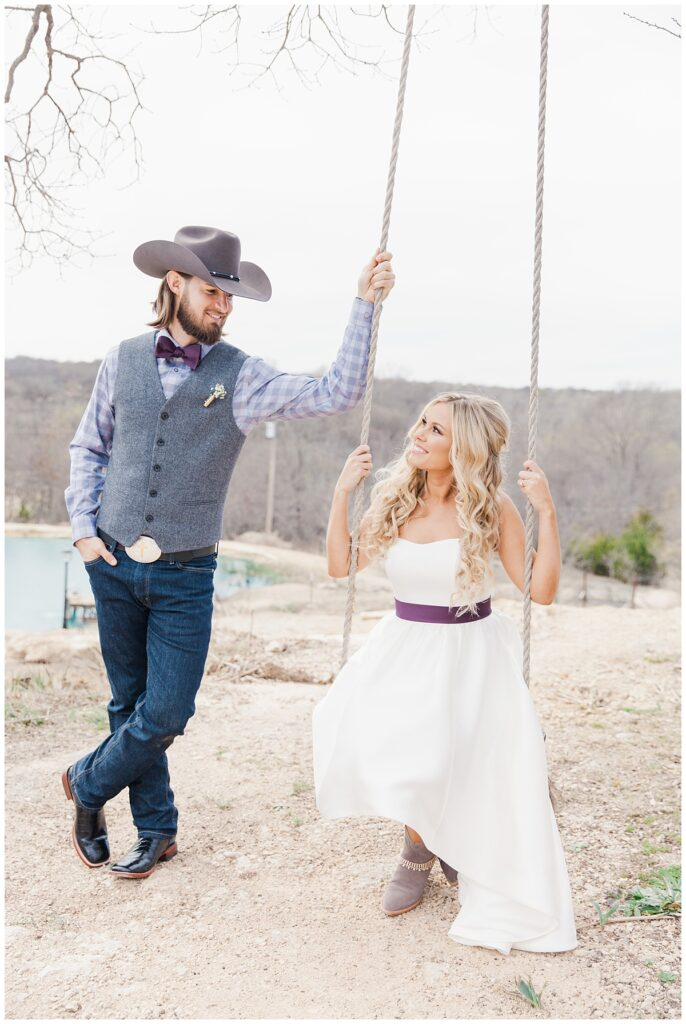 Cowboy groom and bride gazes at one another for bridal portrait for outdoor Texas styled wedding at Fort Worth Country Memorial Wedding Venue photographed by Dallas wedding photographer Jenny Bui of Picture Bouquet Studio.