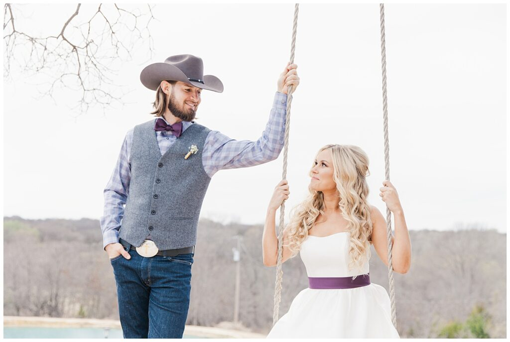 Texas styled bride and groom looks at one another on swing for outdoor Texas styled wedding at Fort Worth Country Memorial Wedding Venue photographed by Dallas wedding photographer Jenny Bui of Picture Bouquet Studio.