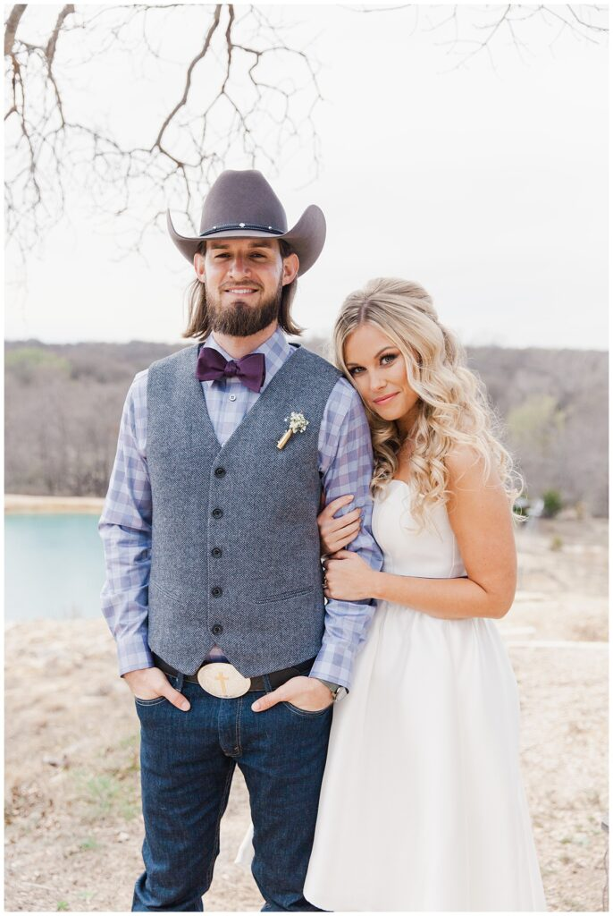 Texas styled bride hugs groom in cowboy hat arms for outdoor Texas styled wedding at Fort Worth Country Memorial Wedding Venue photographed by Dallas wedding photographer Jenny Bui of Picture Bouquet Studio.