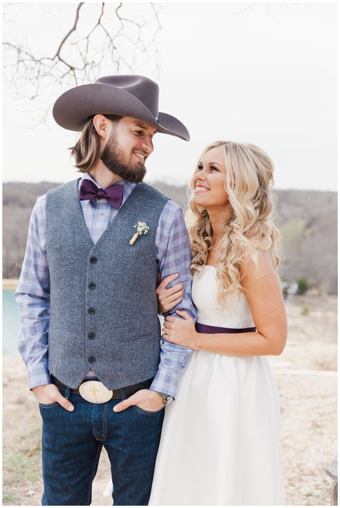 Texas styled bride and groom looks at one another for outdoor Texas styled wedding at Fort Worth Country Memorial Wedding Venue photographed by Dallas wedding photographer Jenny Bui of Picture Bouquet Studio.