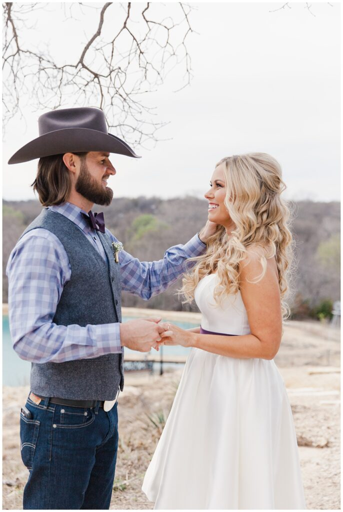 Texas styled bride and groom in coordinating purple color palette stares at one another for bridal portrait for outdoor Texas styled wedding at Fort Worth Country Memorial Wedding Venue photographed by Dallas wedding photographer Jenny Bui of Picture Bouquet Studio.