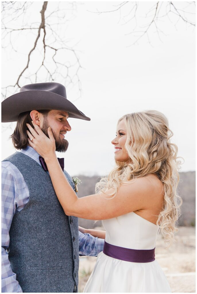 Texas bride caresses grooms cheek for bridal portraits for outdoor Texas styled wedding at Fort Worth Country Memorial Wedding Venue photographed by Dallas wedding photographer Jenny Bui of Picture Bouquet Studio.