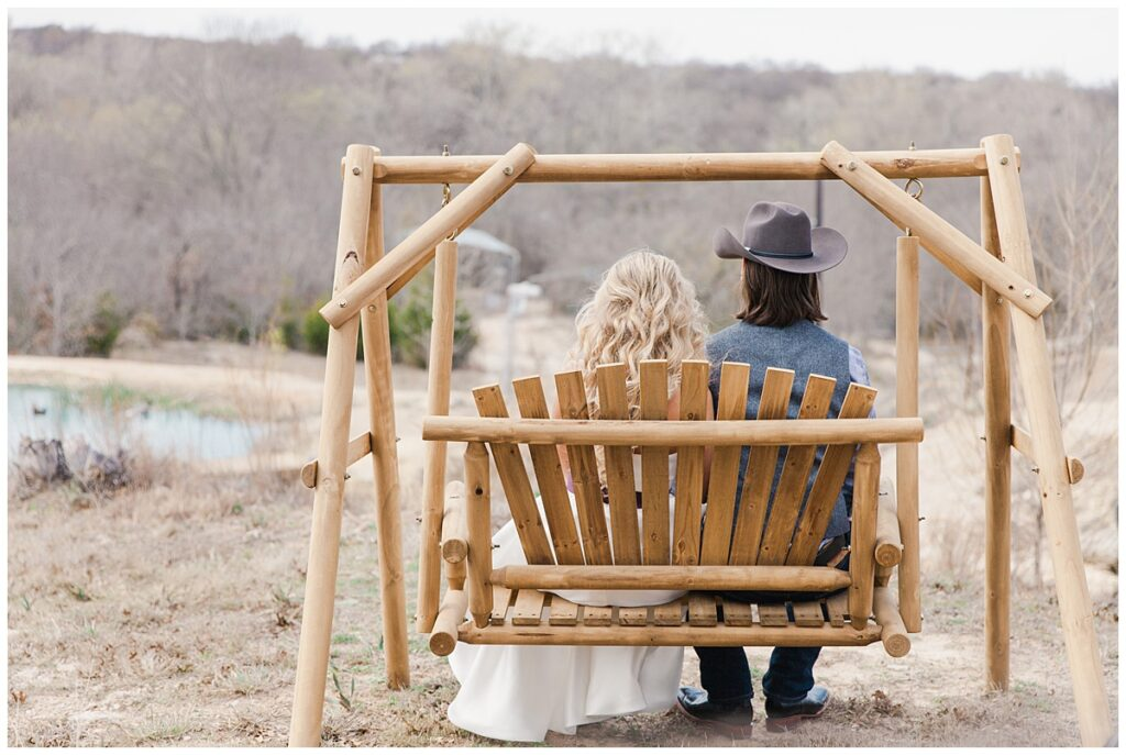 Texas styled bride and groom sits on swinging bench and gazes into the distance for outdoor Texas styled wedding at Fort Worth Country Memorial Wedding Venue photographed by Dallas wedding photographer Jenny Bui of Picture Bouquet Studio.