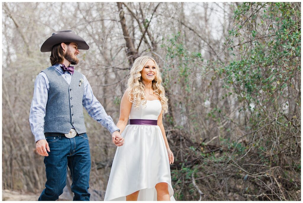 Texas styled bride and groom walk along pathway holding hands for outdoor Texas styled wedding at Fort Worth Country Memorial Wedding Venue photographed by Dallas wedding photographer Jenny Bui of Picture Bouquet Studio.