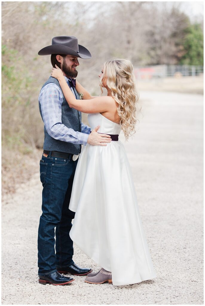 Texas styled bride and groom dances on pathway for bridal portrait for outdoor Texas styled wedding at Fort Worth Country Memorial Wedding Venue photographed by Dallas wedding photographer Jenny Bui of Picture Bouquet Studio.