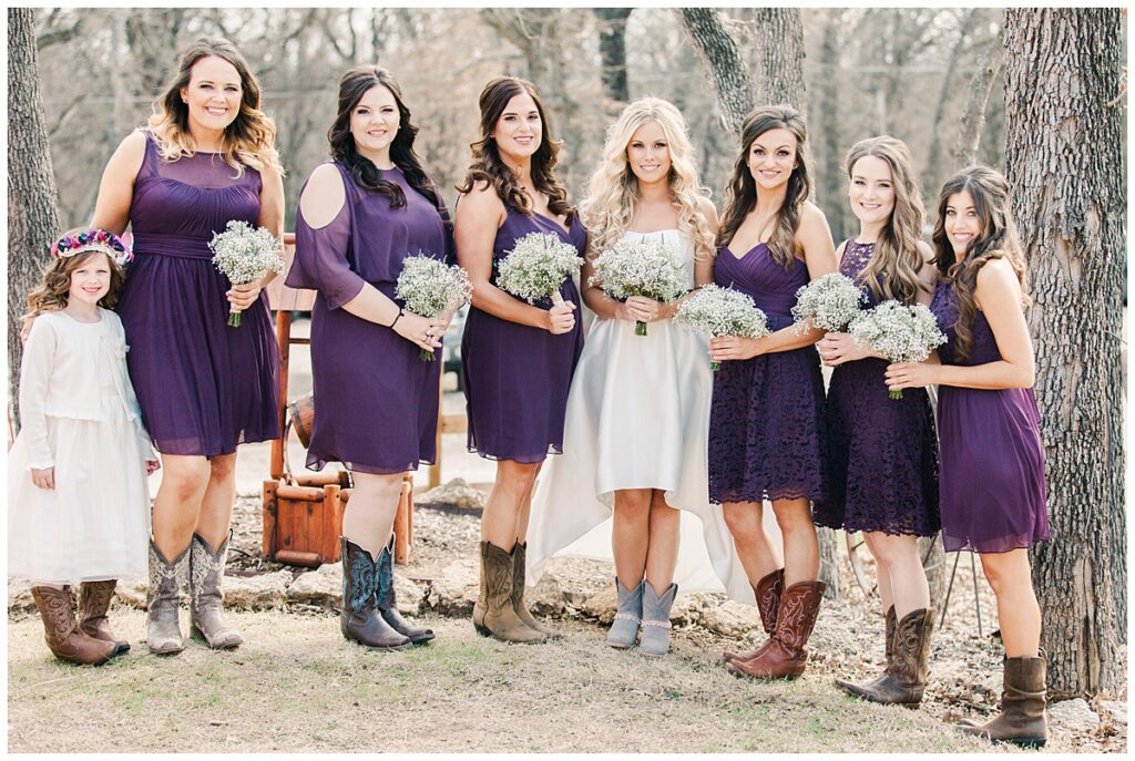 Texas styled bridesmaid in purple dresses and cowboy boots poses for outdoor Texas styled wedding at Fort Worth Country Memorial Wedding Venue photographed by Dallas wedding photographer Jenny Bui of Picture Bouquet Studio.