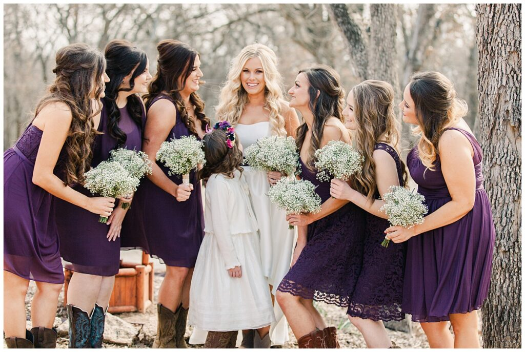 Texas styled bridesmaid poses with bride in purple bridesmaids dresses and baby's breaths bouquet for outdoor Texas styled wedding at Fort Worth Country Memorial Wedding Venue photographed by Dallas wedding photographer Jenny Bui of Picture Bouquet Studio.