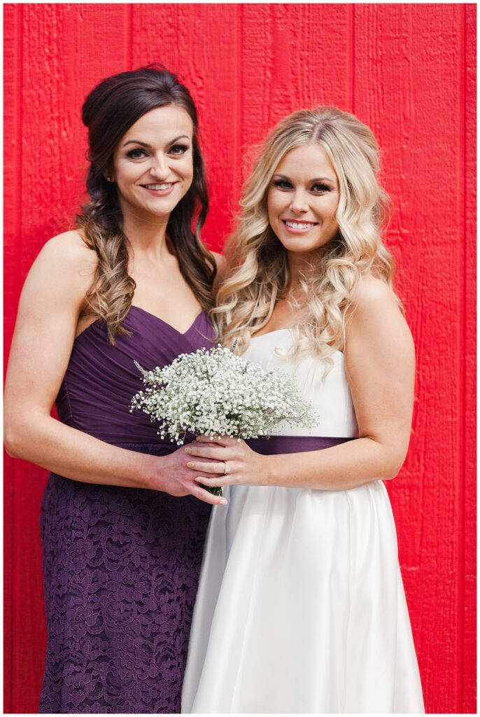Texas styled bridesmaid poses with bride in purple bridesmaids dresses and baby's breaths bouquet in front of red barn for outdoor Texas styled wedding at Fort Worth Country Memorial Wedding Venue photographed by Dallas wedding photographer Jenny Bui of Picture Bouquet Studio.