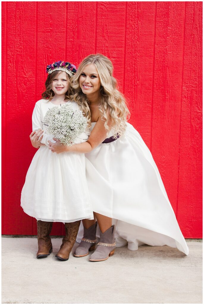 Texas styled bride poses in front of barn with flower girl in front of red barn for outdoor Texas styled wedding at Fort Worth Country Memorial Wedding Venue photographed by Dallas wedding photographer Jenny Bui of Picture Bouquet Studio.