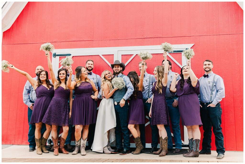 Texas styled bridal party poses with bride and groom in front of red barn for outdoor Texas styled wedding at Fort Worth Country Memorial Wedding Venue photographed by Dallas wedding photographer Jenny Bui of Picture Bouquet Studio.