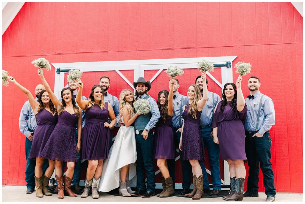 Texas styled bridal party cheers for  bride and groom in front of red barn for outdoor Texas styled wedding at Fort Worth Country Memorial Wedding Venue photographed by Dallas wedding photographer Jenny Bui of Picture Bouquet Studio.