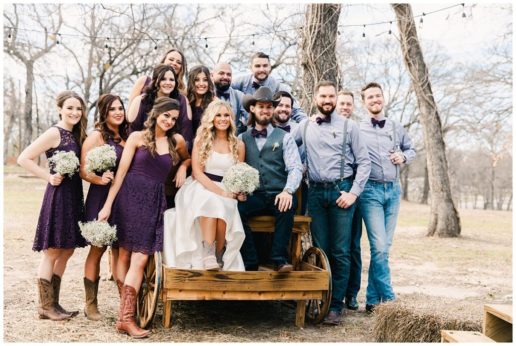 Texas styled bridal party poses with bride and groom on wagon for outdoor Texas styled wedding at Fort Worth Country Memorial Wedding Venue photographed by Dallas wedding photographer Jenny Bui of Picture Bouquet Studio.